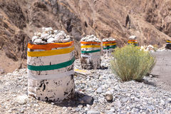 Road block. A concrete road block with colorful flags covering in rocky mountain in Leh, Ladakh, India Stock Photo