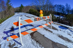 Road block set up before snowy and icy road Royalty Free Stock Images