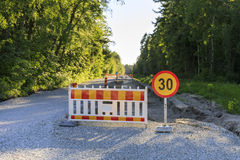 Road block and a sign at road construction. Road block and a speed limit sign on a road under construction Royalty Free Stock Images