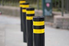 Road blocker. Aligned yellow and black poles royalty free stock photos