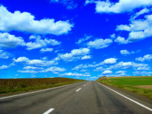 Road and the blue sky. Empty asphalted highway with blue sky and white clouds Royalty Free Stock Image