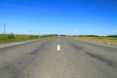 Road and blue sky summer landscape. In the sunny day Royalty Free Stock Photo