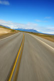 Road Blur. Image of tilted, blurred road with blue sky and mountains in the background Stock Images