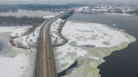 Road bridge across the Dnieper River in Dnipro city at winter time. Aerial top view on road bridge across the Dnieper River in Dnipro city at winter time. Dnepr stock photo