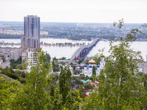 Road bridge across the Volga river between the cities of Saratov and Engels. The city`s skyline. An Orthodox Church. May Stock Photography