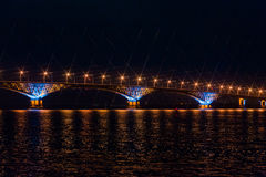 Road bridge across the Volga river between the cities of Saratov and Engels, Russia. Night or evening landscape. Golden street lights. The reflection in the stock photos