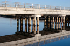 Road bridge over cold river reflected Stock Photography
