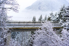 Road bridge or viaduct in snowy mountains. Passing through snow-covered winter trees and forests with mist or cloud in the background stock photos