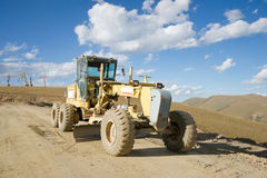 Road building machine with highland landscape Royalty Free Stock Images