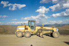Road building machine with highland landscape Royalty Free Stock Photography