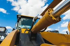 Road-building machinery, tractors yellow excavators in open air in working position. Excavator Loader Machine. Side View of Front Hoe Loader. Industrial Vehicle Stock Photo