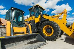 Road-building machinery, tractors yellow excavators in open air in working position