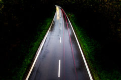 ROAD WITH CAR ALONE AT NIGHT WITH BLURRY LIGHTS Stock Image