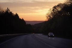 Road with car drive in mountains, forest on sunset sky. Transport, transportation, adventure, discovery. Travel, traveling, travelling, journey, trip Royalty Free Stock Images