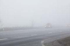 Road and a car in fog Royalty Free Stock Images
