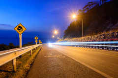 The road with car lights on the hill near the coast at night Royalty Free Stock Images