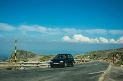 Road and car over hilly landscape covered by rocks. Serra da Estrela, Portugal - July 12, 2018. Car crossing road on hilly landscape covered by rocks, at the stock photos