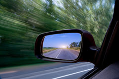 Road in car side-view mirror. Details of road reflected in travelling car side-view mirror with blurred background Royalty Free Stock Photos