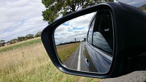 Road in car side-view mirror Stock Images