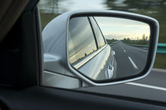 Road in car side-view mirror. Details of road reflected in travelling car side-view mirror with blurred background Royalty Free Stock Photo