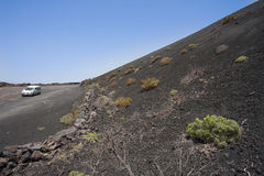 Road with car beside volcanic ashes mountain Stock Images