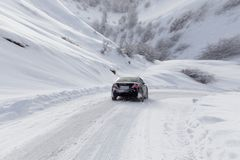Road with a car in winter in the mountains.  stock photos