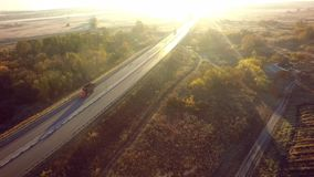 Road for cars aerial view from top around green nature. And sun ray stock photos
