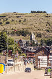 Road with cars circulating in Catalonia. There are church with towerbell. In the background the mountains of the Pyrenees. It is a vertical picture on a sunny Stock Image