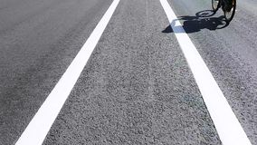 Road without cars close-up on the dividing strip on which the cyclist and a man ride an electric scooter. stock footage