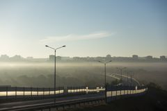 Road for cars in fog with city background.  royalty free stock image