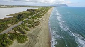 Road is for cars located along the coast leading to the mountains. Aerial survey. Slow motion. Road is for cars located along the coast on one side and bay on stock footage