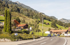 Road with cars. With wooden houses in Switzerland. Alpine mountains in the background are on a cloudy day. It´s a editorial picture Stock Images