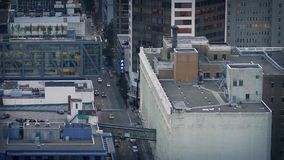 Road Through The City In The Evening. Overhead view of road with cars passing through tall buildings in low light stock footage