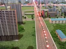 A road through the city in miniature. Road, buildings, houses, red led lights, and trees in a miniature model city, architecture Royalty Free Stock Photos