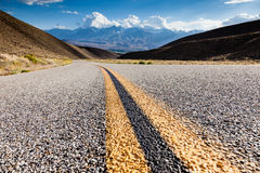 Road close-up in California. Highway in California with distant mountains on the horizon Royalty Free Stock Images