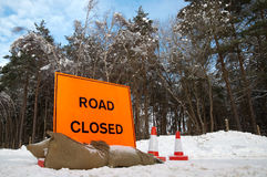 Road closed. Fluorescent orange road sign on a snow covered highway (portrait crop also available royalty free stock photography