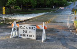 Road Closed. Due to high water sign with flooded road in background royalty free stock photography