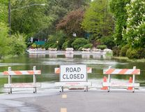 Road Closed. A Road Closed sign stands in front of flood waters from a nearby river, Washington State Royalty Free Stock Image
