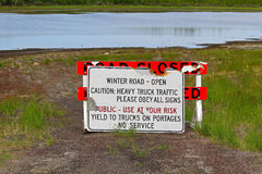 A road closed barricade and a winter road open sign leaning against each other Royalty Free Stock Photos