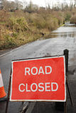 Road closed due to flooding. A country road is closed as a swollen river breaks its banks. Hampshire, England UK Stock Photo