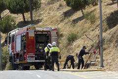 Road closed by a fire and firefighters working Stock Photo