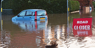A road closed at a flooded Road. A flooded road junction with a Road Closed sign and a sunken car Royalty Free Stock Photography