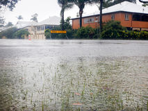 Road Closed for Flooding. Road Closed sign at the end of a flooded street in Brisbane, Australia.  In the foreground in a large flood puddle with grass and Stock Images