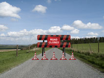Road closed. Sign on barrier due to resurfacing work on single country lane through countryside and farmland Stock Images