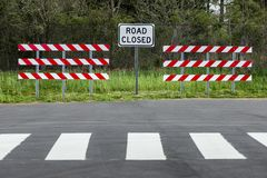 Road Closed Sign and Barriers. Horizontal shot of two red and white striped barriers with a road closed sign in the middle of them. There is a wooded area behind stock photo