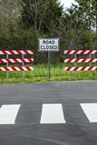 Road Closed Sign With Barriers. Vertical shot of two red and white striped barriers with a road closed sign in the middle of them royalty free stock image