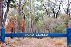 Road closed sign blocking vehicles on gravel dirt of bush forest. A bold timber road closed sign stops and is blocking all vehicles and motor cars from driving Royalty Free Stock Photo