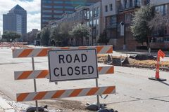 Road closed sign in Downtown Irving, Texas, USA. Close-up road closed sign in Downtown Irving, Texas, USA. Barricade closures, cones with urban buildings in Stock Photography