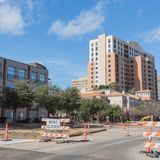 Road closed sign in Downtown Irving, Texas, USA. Under cloud blue sky. Barricade closures, cones with construction equipments and high-rise building in Royalty Free Stock Photos