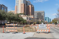 Road closed sign in Downtown Irving, Texas, USA. Under cloud blue sky. Barricade closures, cones with construction equipments and high-rise building in Stock Photography